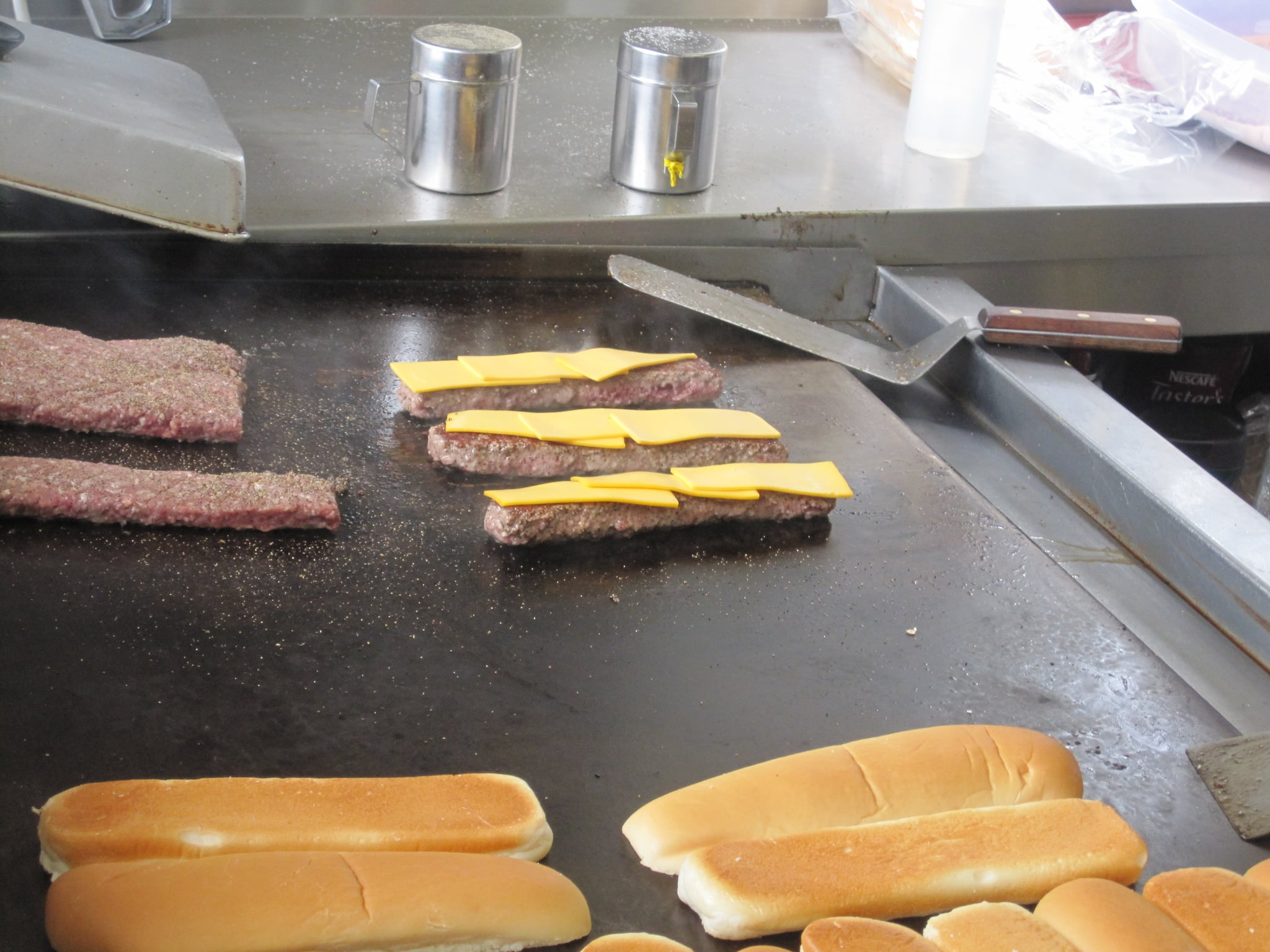 Back to the burger! After a quick flip, the patties are topped with thick narrow slices of American cheese.