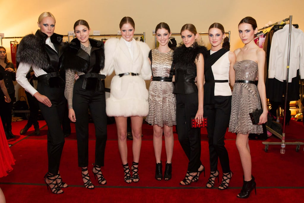Models posed together backstage before hitting the runway.