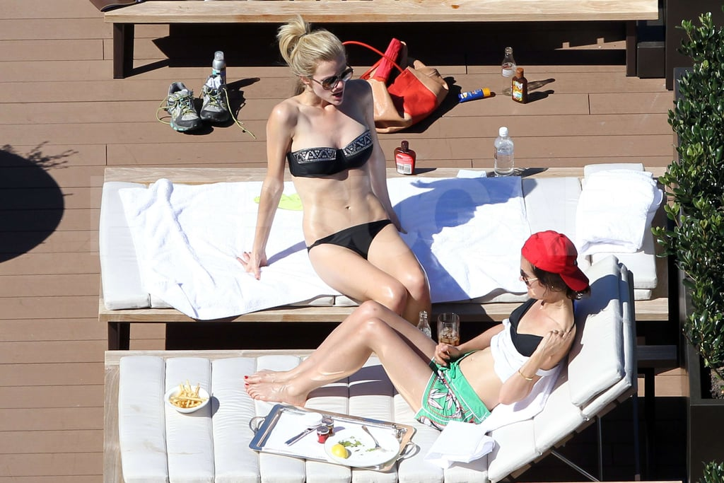 Brooklyn Decker laid by the pool in a black bikini in Australia.