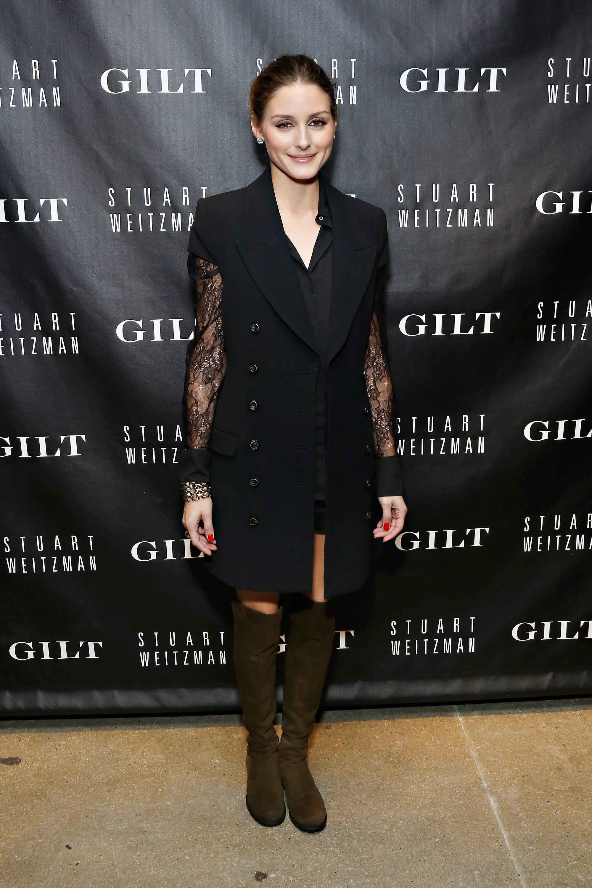 Olivia outfitted a chic sleeveless coat with knee-high Stuart Weitzman boots at the anniversary celebration for the 5050 Boot in October.