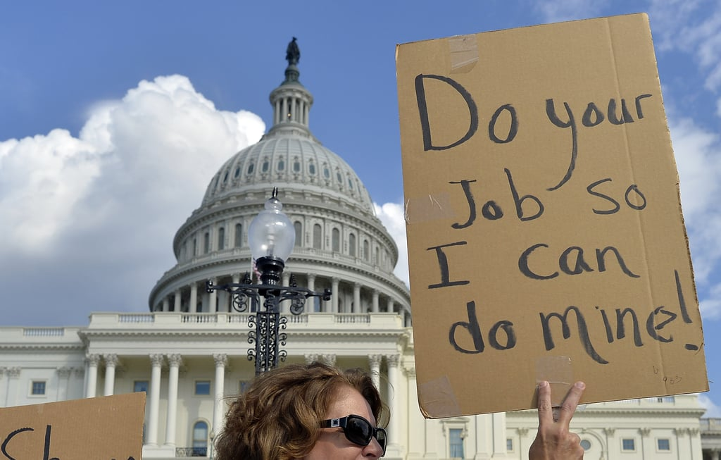 """On the steps of the US Capitol, a woman help up a sign that read, """"Do your job so I can do mine."""""""