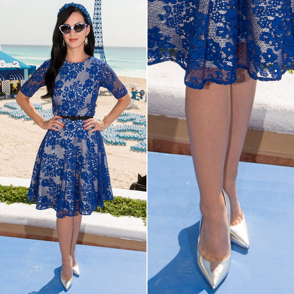 Katy Perry flew to Cancun to get in on the Smurfs 2 fun wearing a fitting blue lace Dolce & Gabbana fit-and-flare dress with silver metallic pointy Jimmy Choo pumps. Her blue accessories — a floral headband and printed cat-eye sunglasses — added further flair.