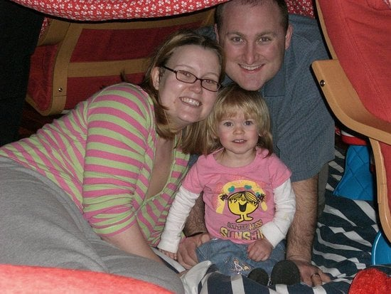 In a fort with her Mama and Daddy.