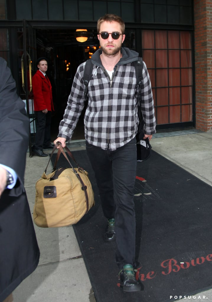 Robert Pattinson carried his luggage out of his hotel after a short stay in the Big Apple.