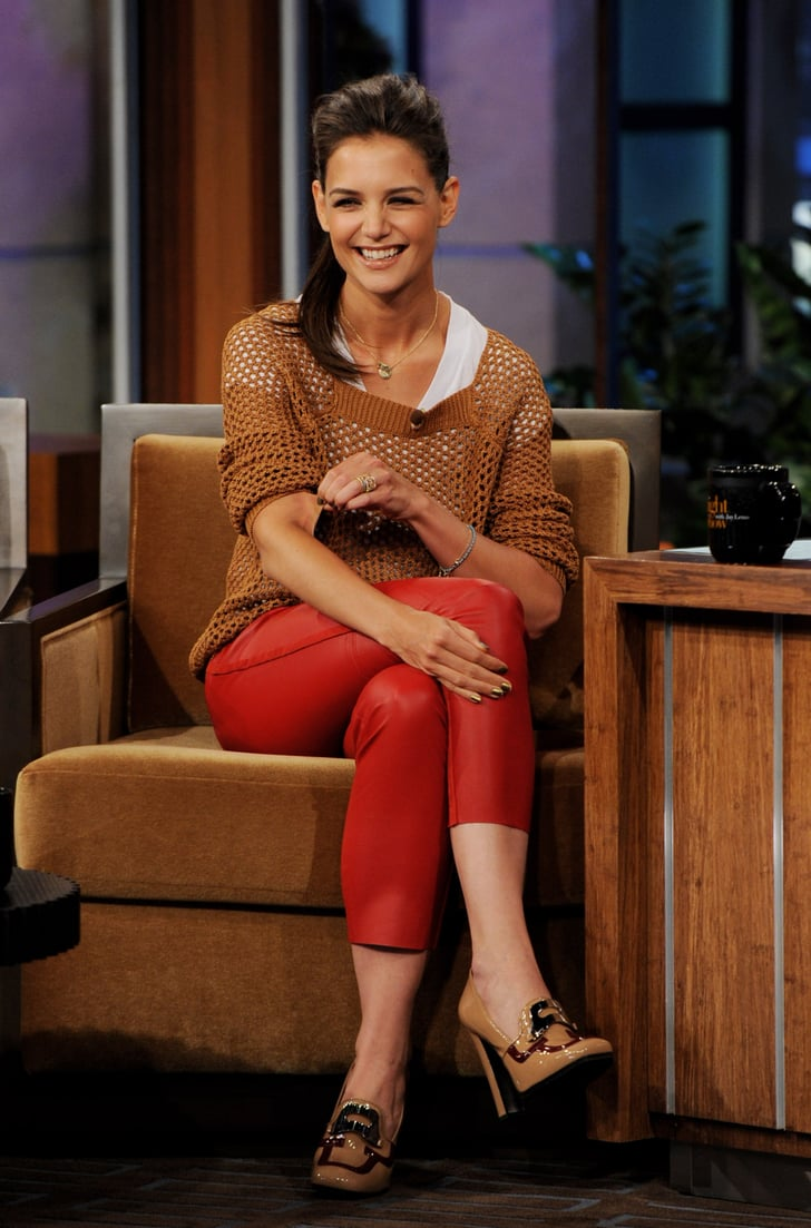Katie Holmes laughs in red leather pants.