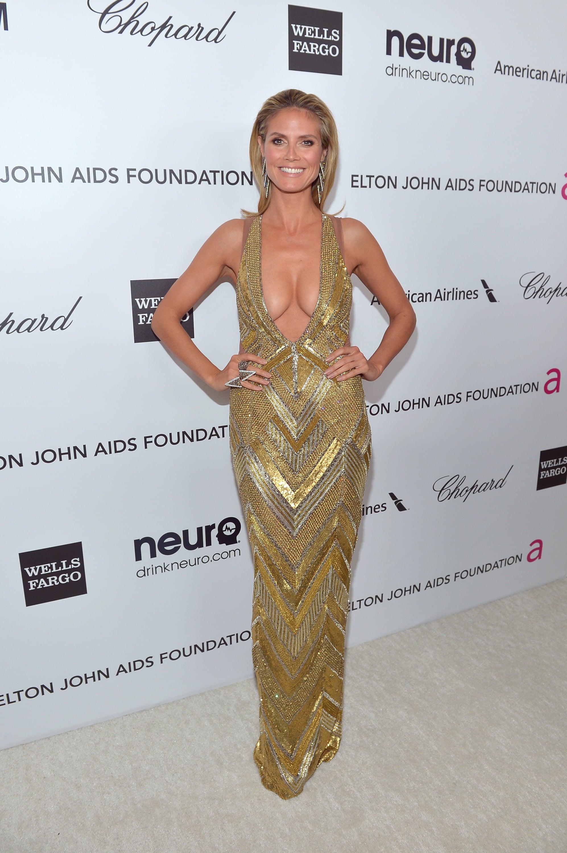 Heidi Klum wore a revealing gold dress to Elton John's Oscar party.