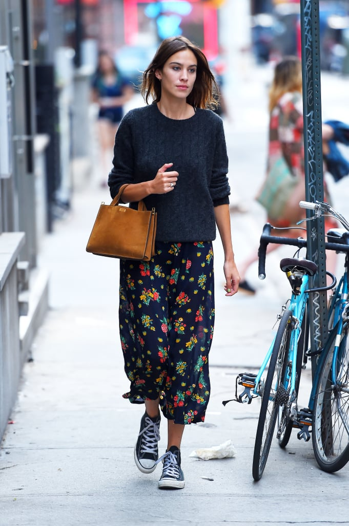 Alexa Chung in a navy floral skirt, sweater, and converse sneakers