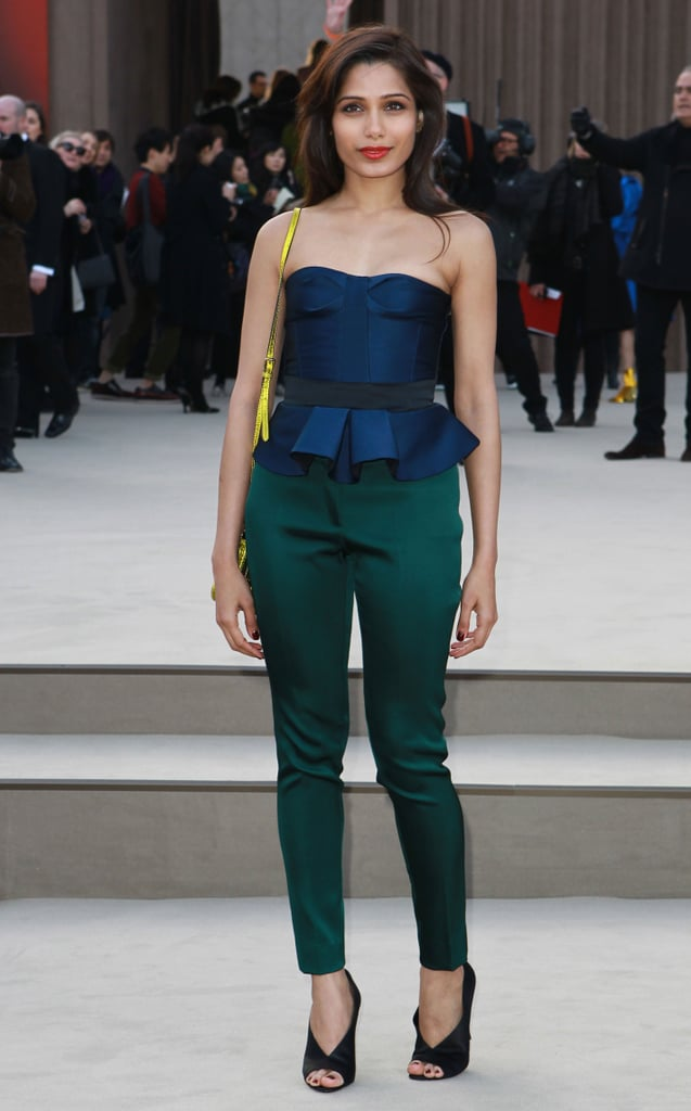 Freida Pinto glowed in a navy satin peplum top and cropped emerald-green trousers, finished with a pop of yellow at Burberry Prorsum.