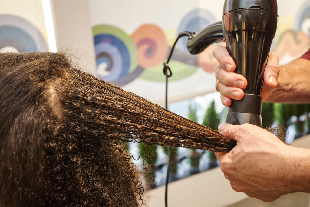 """After prepping hair with Hair Rules Blow It All Out ($16) to fight humidity, Dickey sectioned off the hair and began to blow-dry.  To ensure that there will be minimal tangling and maximum protection, Dickey suggested using a comb attachment. """"[This way,] there is no extra tension on the hair — you're basically just detangling,"""" he explained. """"And it's always moving, so it's not burning your hair."""""""