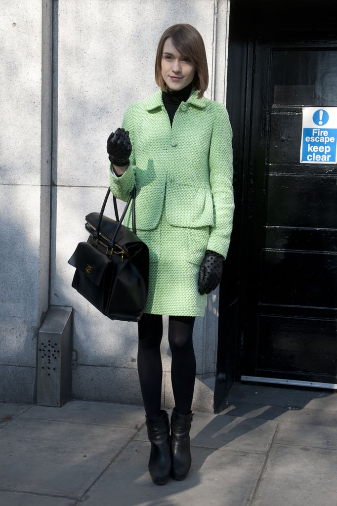A ladylike suit was anchored with this attendee's black tights, turtleneck, and satchel.