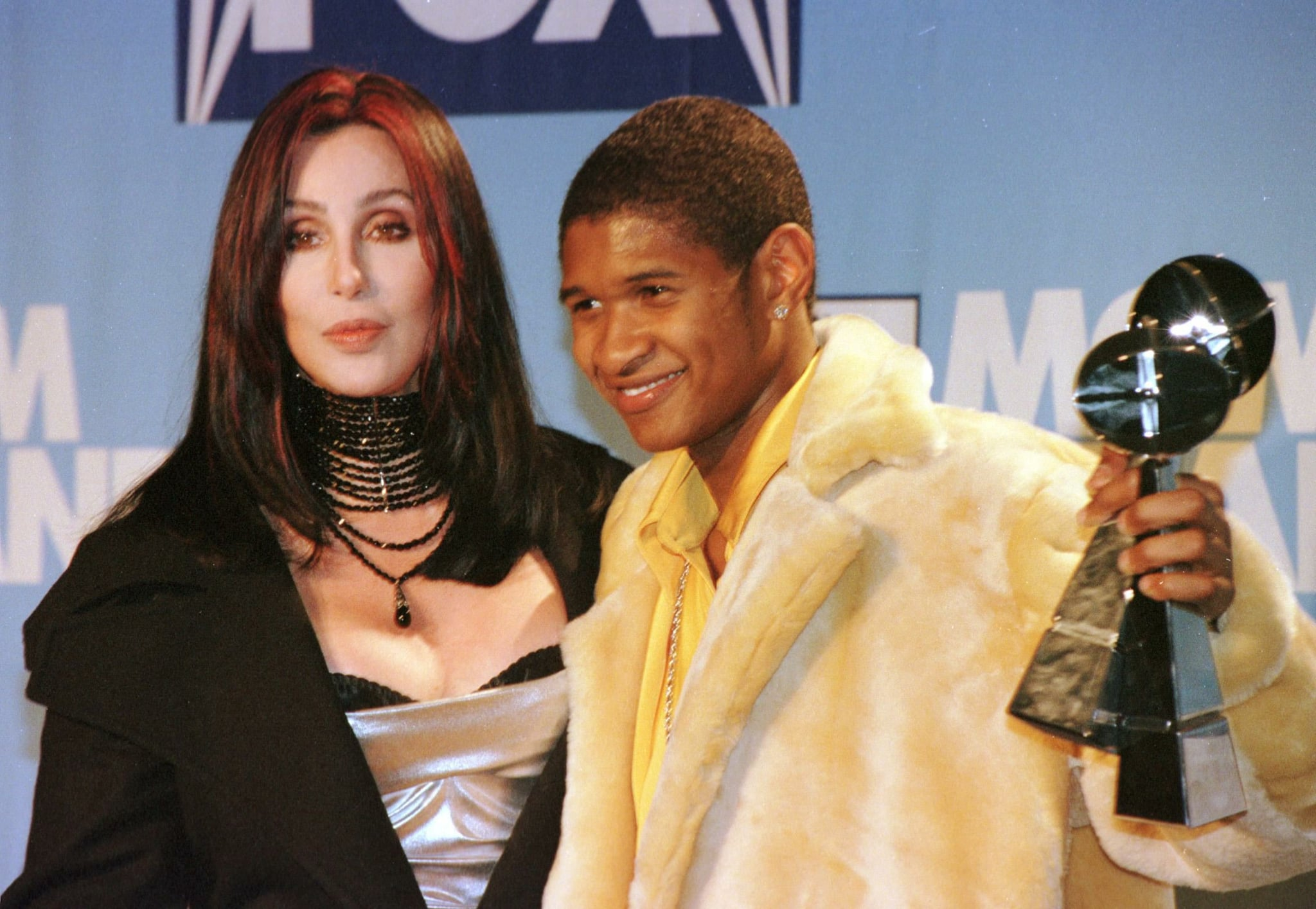 Usher showed off his artist of the year Billboard award next to Cher in December 1998.