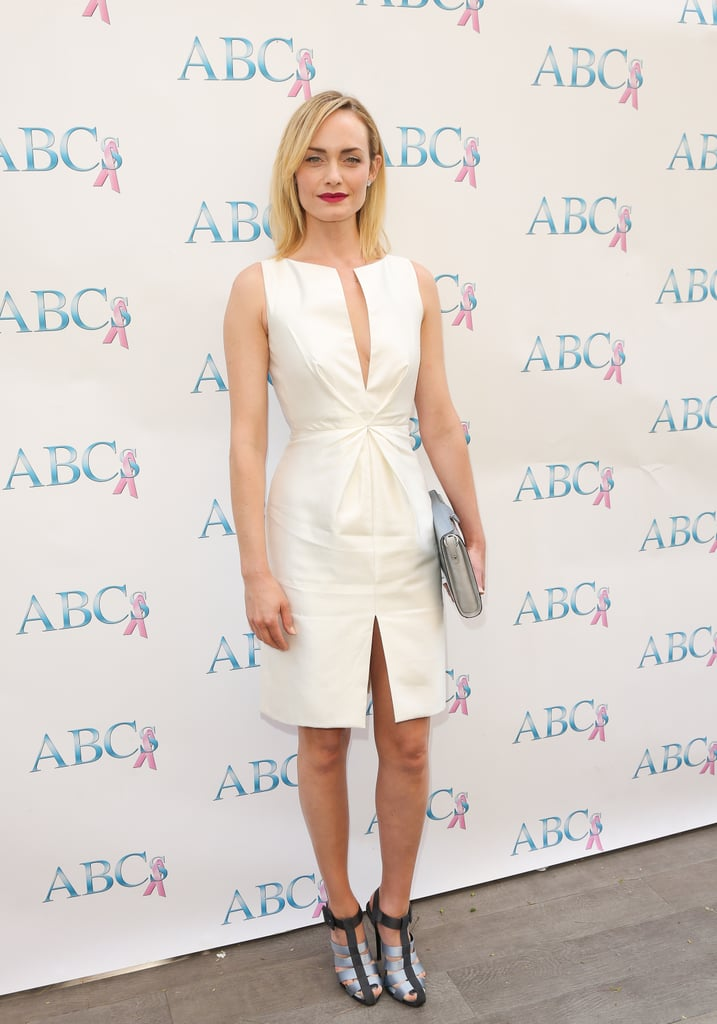 Amber Valletta attended a Mother's Day luncheon in Beverly Hills in a crisp little white dress with two slits: one the bodice and one on the skirt. She added further spunk via a metallic clutch and two-toned caged sandals.