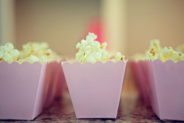 Have a popcorn bar station for guests to add their own seasonings. And mini pink boxes make it even cuter.
