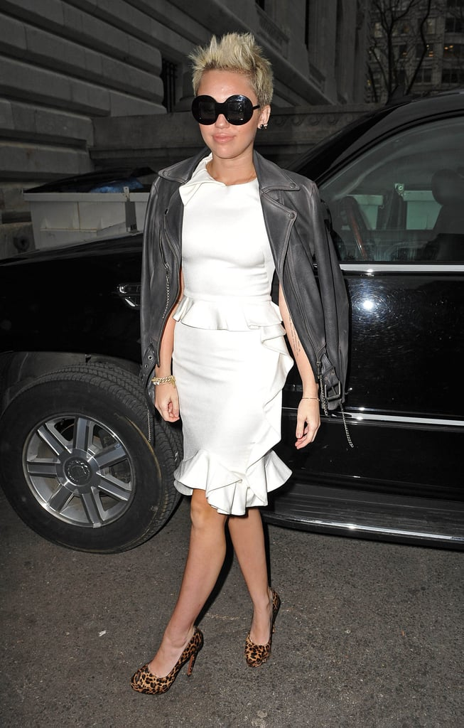 Miley Cyrus edged up her pristine white peplum dress with a gray leather topper and leopard pumps on her way into Marchesa.