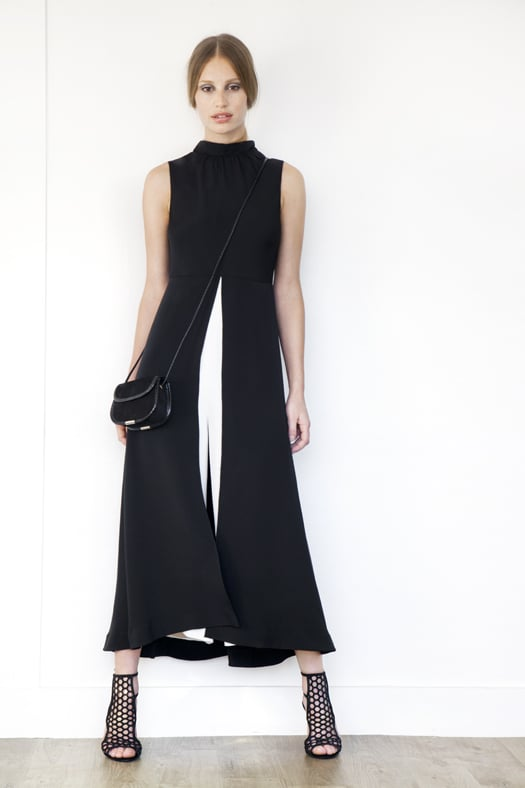 Jumpsuit Dress in Two-Toned Silk in Black & Cream ($1,295), Scandal Suede Sandal Bootie in Black ($895), Treasure Suede Cross Body Bag in Black ($650) Photo courtesy of Tamara Mellon
