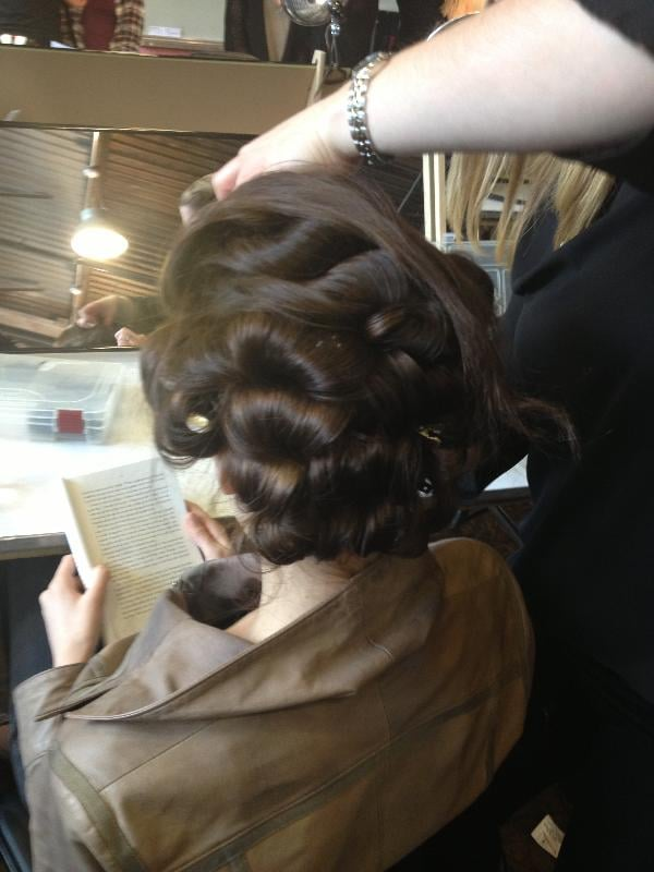The foundation of the low chignon for the Monique Lhuillier bridal runway was a head full of bountiful curls. First, Nina Dimachki, lead hairstylist for Kérastase, applied a potion of Volumactive Mousse, Volumactive Spray, and Ciment Thermique. She then blow-dried hair before curling with a large iron and pinning up curls while still warm.
