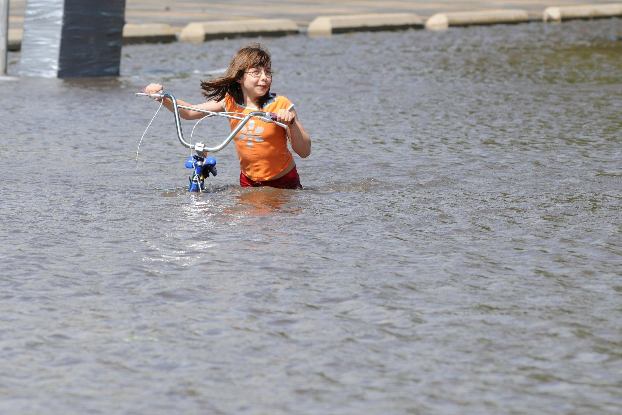 Gabrielle Steenblock, 8, walks across a flooded street near downtown Cedar Rapids.