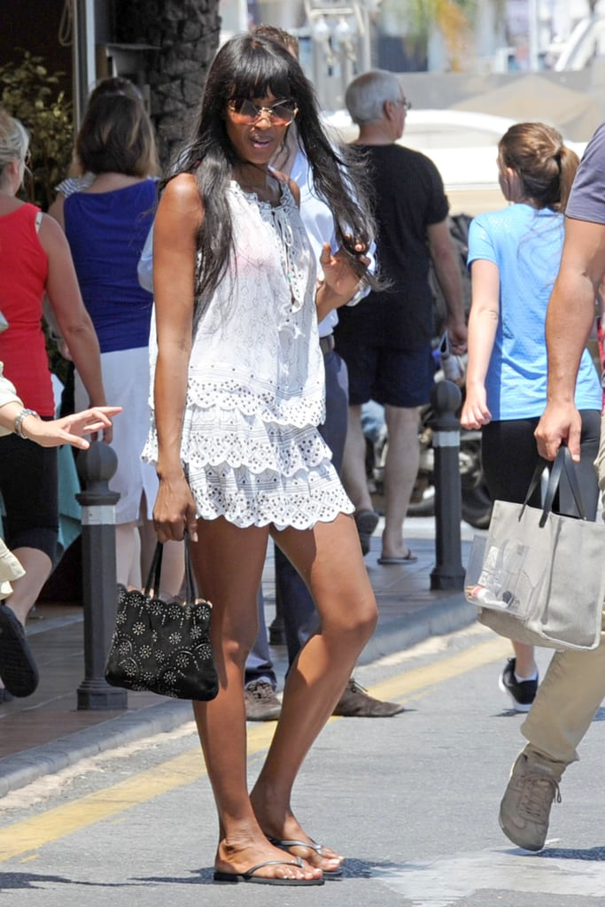 Naomi Campbell vacationed in Marbella looking fresh in a white tiered minidress, a black bag, and gray flip-flops.