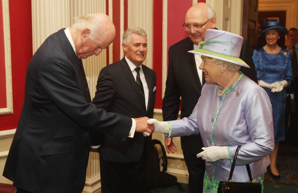 Queen Elizabeth shakes hands with a man during her dinner with the Argyll and Sutherland Highlanders.