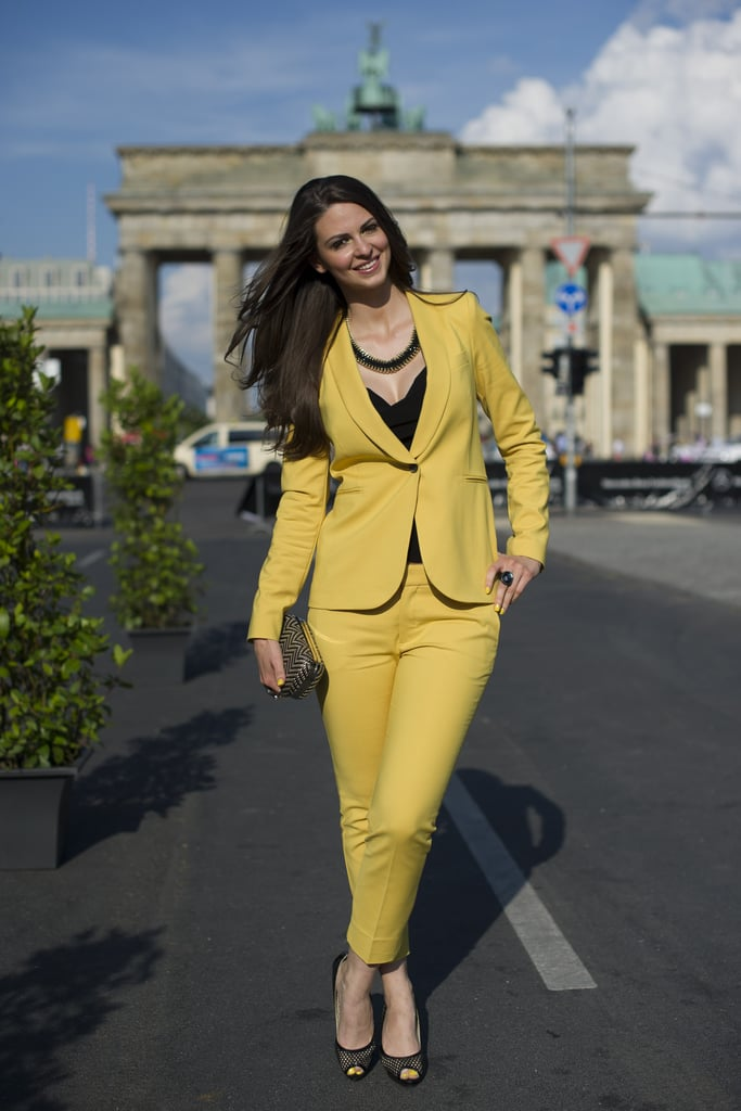This girl tried on a bold yellow pantsuit, then tamed it with black add-ons.