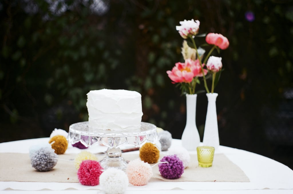 We can't get over how whimsical and stunning this simple cake is with the help of colorful pompoms.