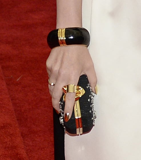 Kylie Minogue wore a gold and black bangle, gold ring, and jeweled black clutch.