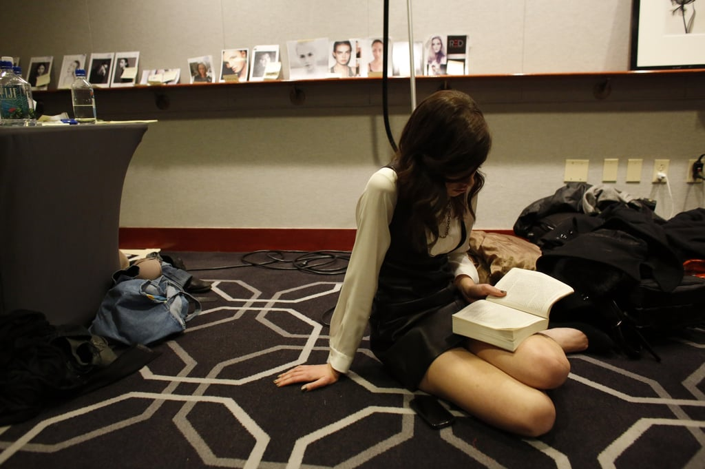 A model sat on the floor backstage at the Whit Fall 2013 presentation and read a book.