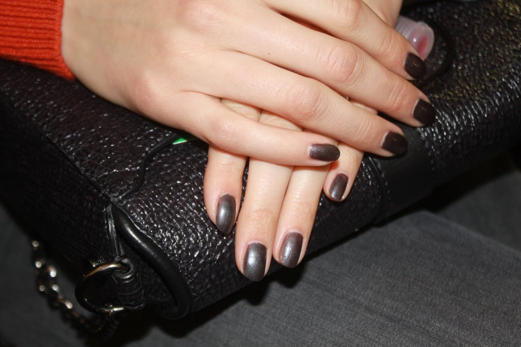 Michelle Saunders, the lead manicurist for Essie, applied one coat of Over the Top on hands to get an icy grey finish. This particular colour was selected because it complemented the embellishments on the clothing. On toes, Stylonomics (a hunter green shade) was applied to match the footwear on the catwalk. Just before the models hit the runway, Saunders dabbed on a bit of cuticle oil for added shine and moisture.
