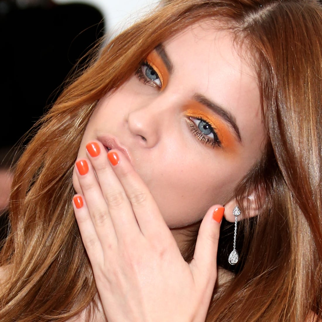 Model Barbara Palvin matched her highlighter orange shadow to her tangerine manicure.