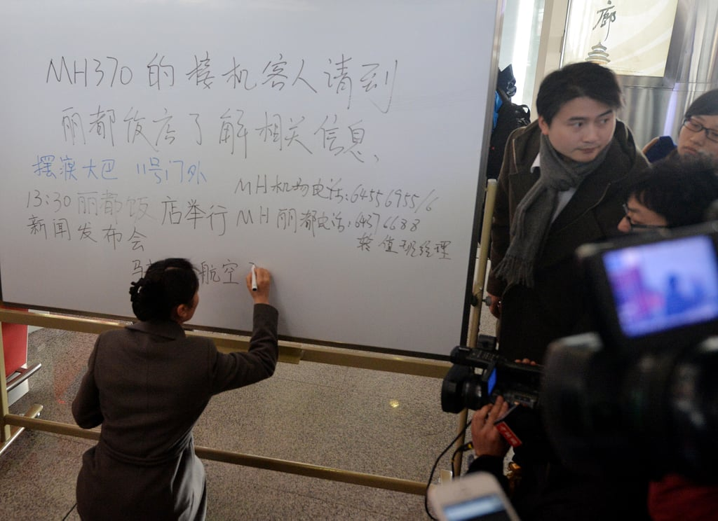 A woman handwrote a message to passengers' families at Beijing Capital International Airport, instructing them to await further information on the flight at a nearby hotel.