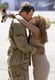 Army Ranger Sgt. Jason Hillebrand kisses his wife, Kelly, after returning from a four-month deployment in Afghanistan.