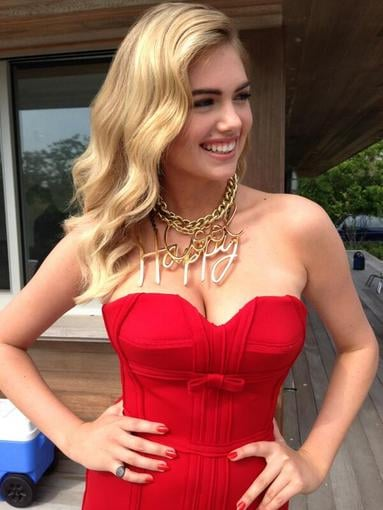 "Kate Upton looked sexy on set in a tight red dress and ""Happy"" gold chain necklace. Source: Twitter user KateUpton"