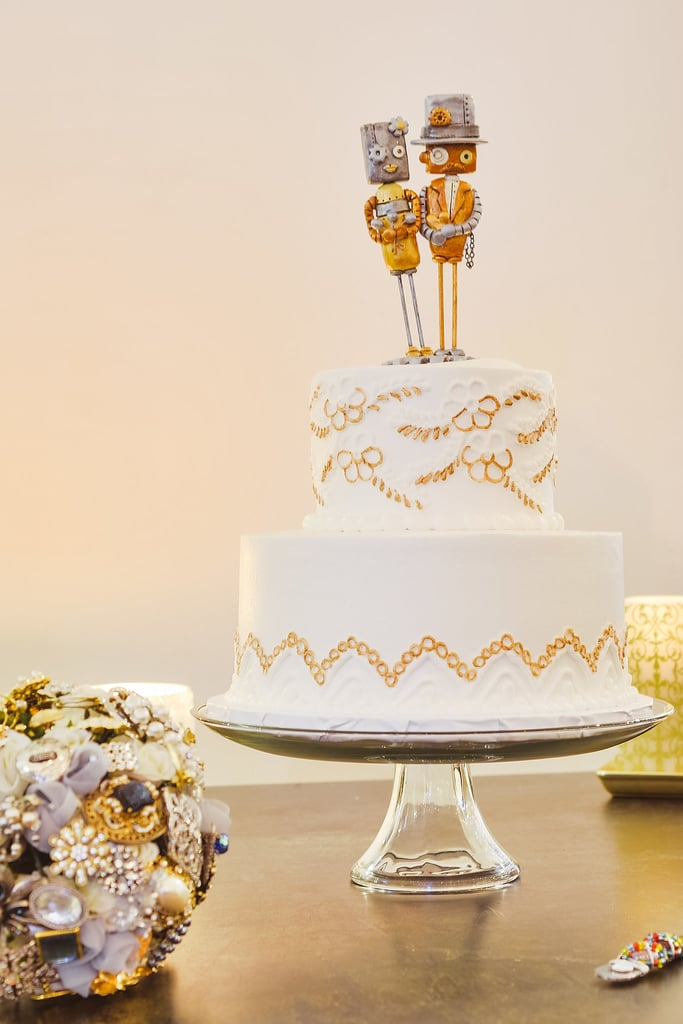 This classic tiered cake looks like it was hand-embroidered with a floral and leaf pattern, and we love that the topper adds a fun, quirky touch.