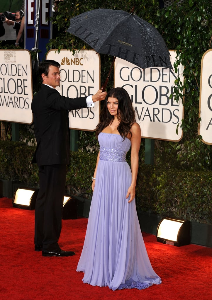Josh Duhamel held out an umbrella for wife Fergie at the Golden Globe Awards in January 2010.