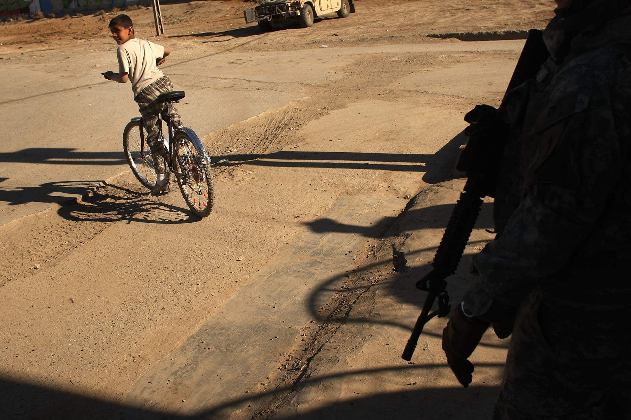 A boy rides his bicycle past US soldiers, March 6, 2008.