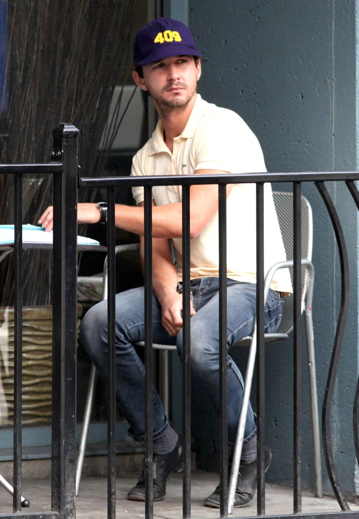 Shia sipped a drink and smoked a cigarette waiting for a friend.