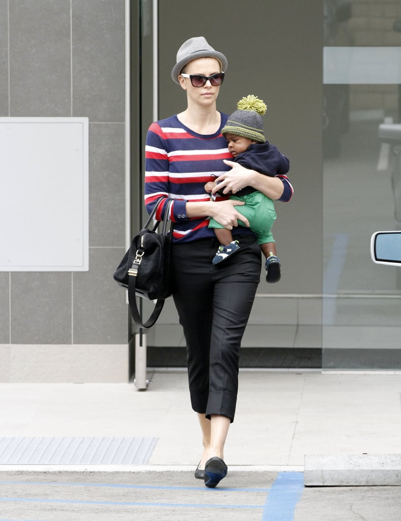 Charlize Theron carried Jackson on one hip and balanced a purse on the other.