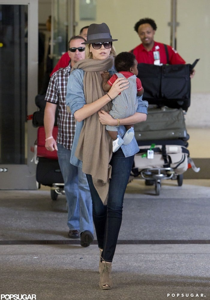 Charlize Theron carried Jackson, who was wearing a pair of overalls.