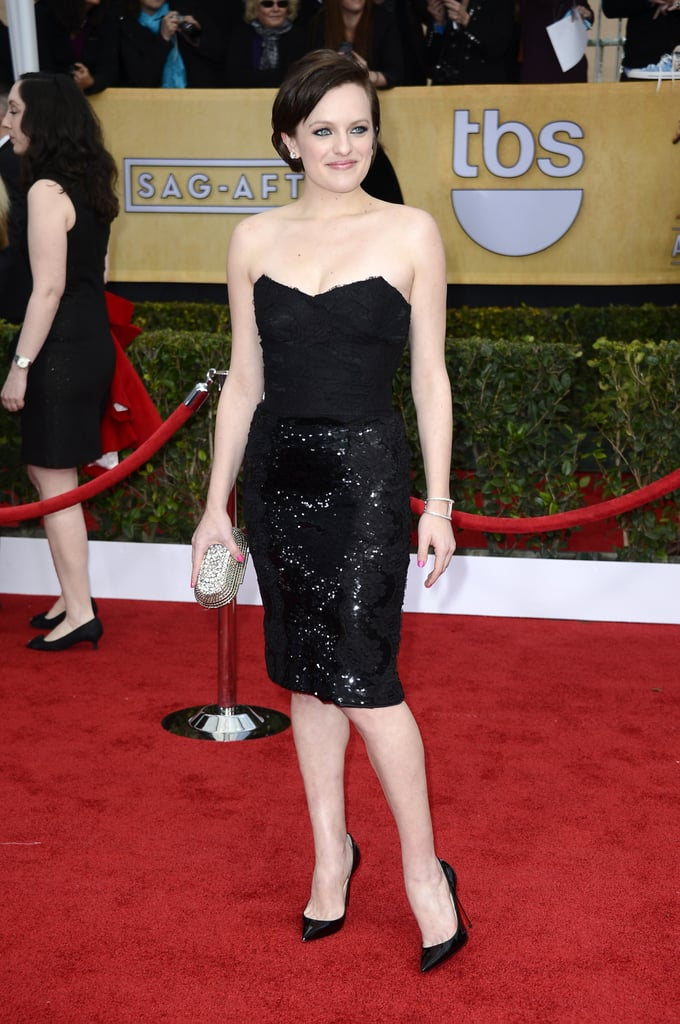 Elizabeth Moss showed a little leg in a black sequin skirt Dolce & Gabbana mini, classic black pumps, a sparkling Jimmy Choo clutch, and one-million-dollar diamond earrings.