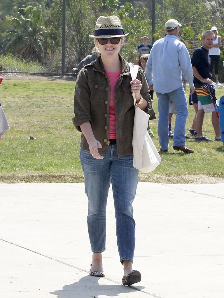 To catch her son's football game, Reese Witherspoon smartly layered up for the sunny afternoon with a lightweight jacket and fedora.