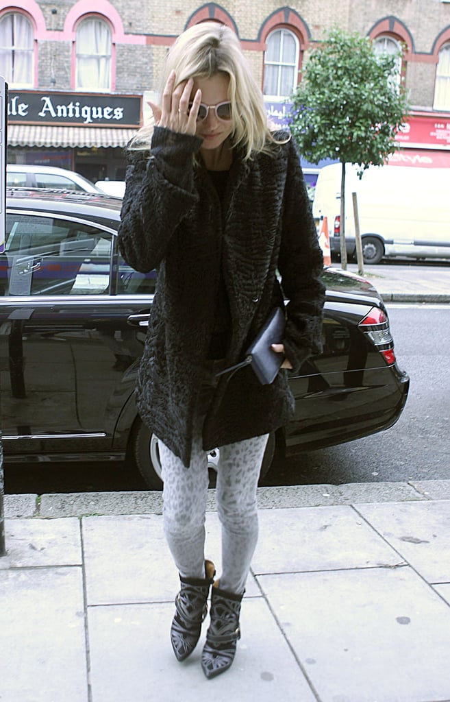 Kate Moss layered up in a plush fur coat, gray leopard skinny jeans, and leather-strap Isabel Marant boots while heading into a movie theater in London.