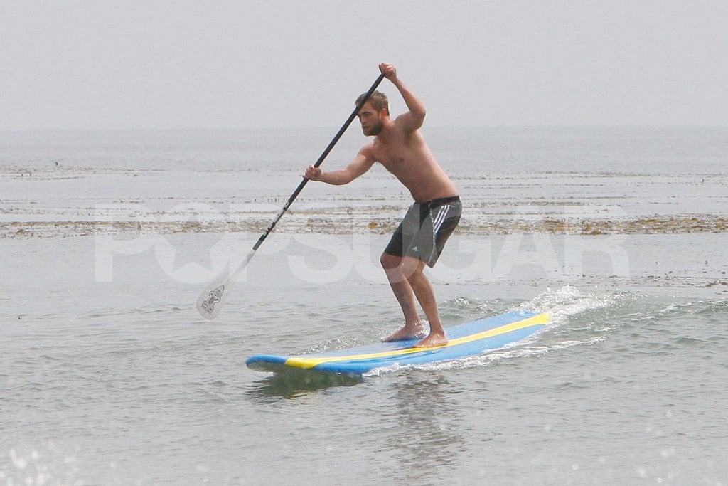 Robert Pattinson surfed shirtless on his paddleboard.