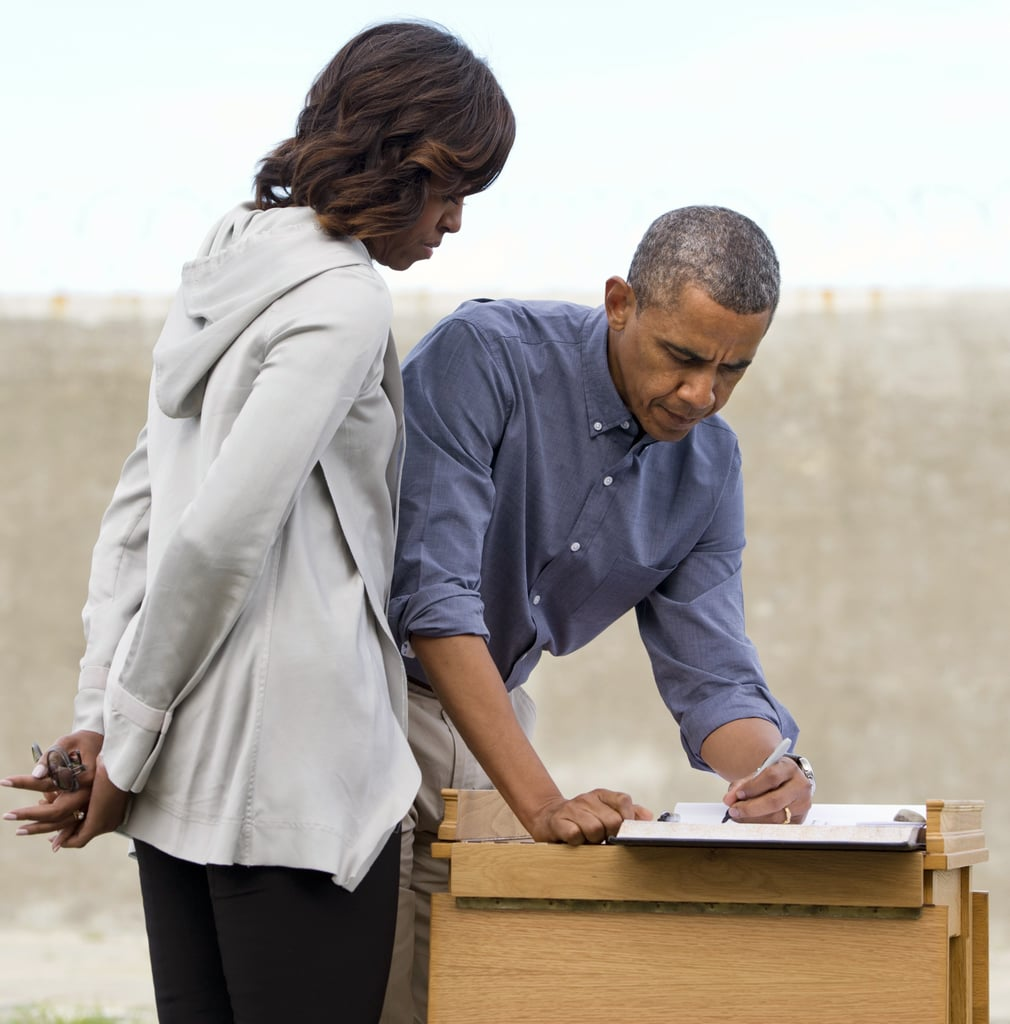 First Lady Michelle Obama looked on as President Obama signed a guest book in the Robben Island prison yard outside Cape Town, South Africa, in June 2013.