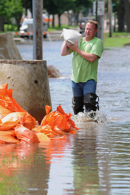 Streets Department employee moves sandbags.