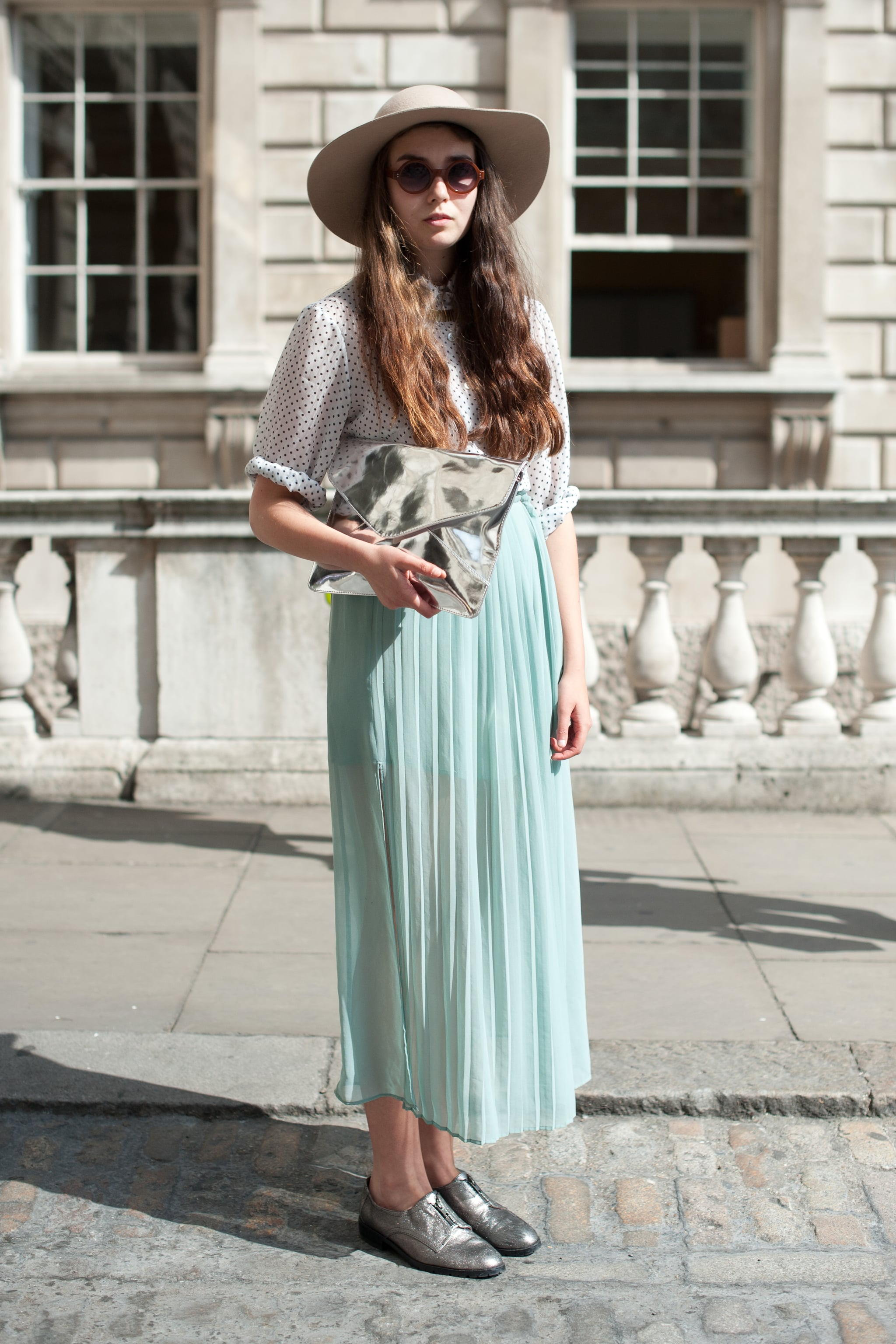 We haven't seen the last of the pretty maxi skirt silhouette — and this street styler wore hers with chic metallic silver oxford flats and a wide-brimmed hat.