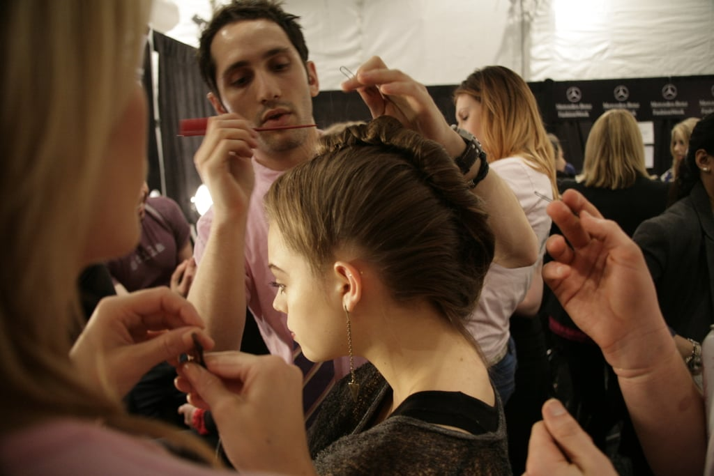 Stylist Devin Toth puts the final touches on a model's coiffure. Photo: Megan Holmes