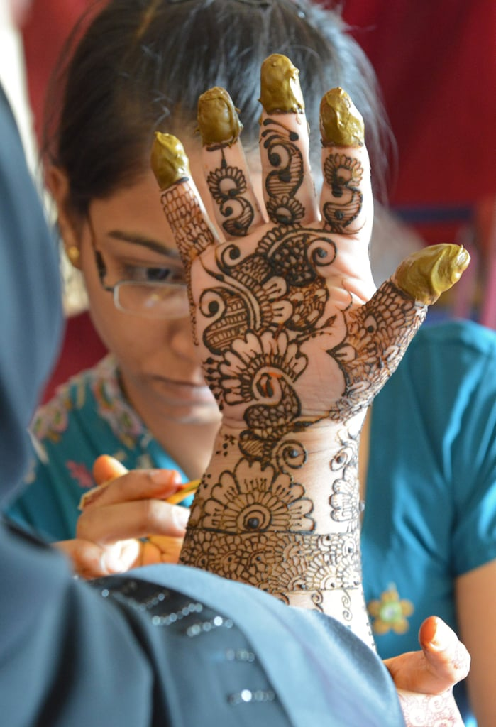 In Hyderabad, India, a woman painted traditional designs on another woman's hands.