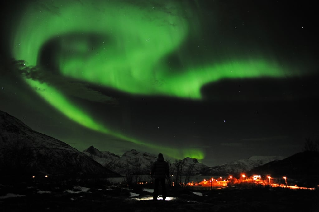 A man checked out the northern lights near the city of Tromsoe, Norway, in January 2012.