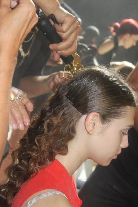 Lead hairstylist Odile Gilbert used a double-barrelled iron to create romantic crimped waves in the back. A modern middle part was gelled and Kérastase Paris Elixir Ultime The Imperial provided an extreme shine.