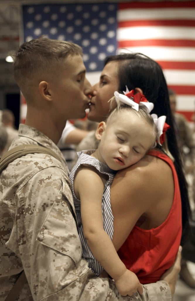 Andrew Thai kisses his wife, Sarah, as his daughter, Mikalah, sleeps, upon his return to Hawaii on June 14, 2010, following a seven-month deployment in southern Afghanistan.